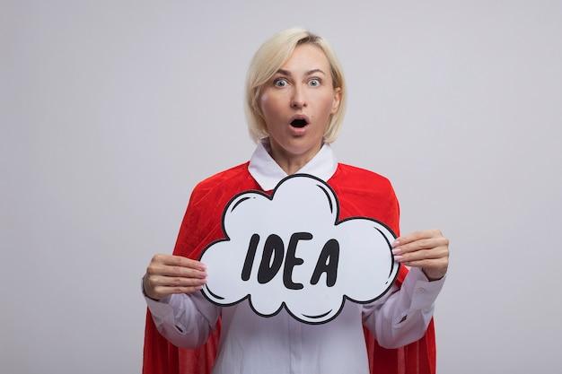 Femme super-héros blonde d'âge moyen surprise en cape rouge tenant une bulle d'idée regardant à l'avant isolée sur un mur blanc