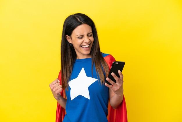 Femme de super héros isolée sur fond jaune à l'aide d'un téléphone portable et faisant un geste de victoire