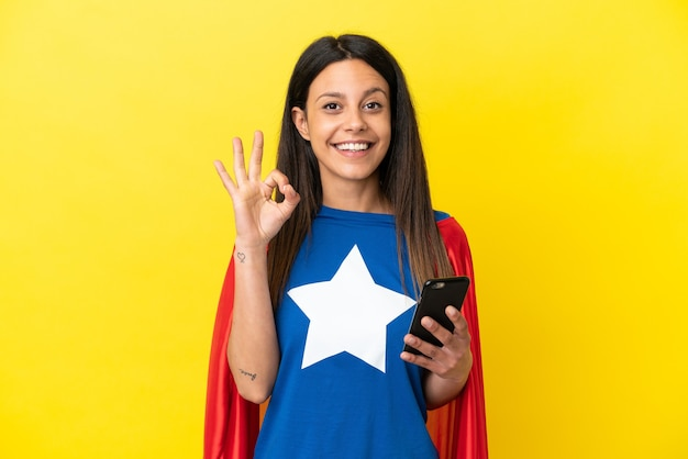 Femme de super héros isolée sur fond jaune à l'aide d'un téléphone portable et faisant signe ok