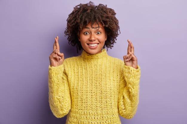Une femme supersitieuse à la peau sombre croise les doigts, sourit largement, prie pour quelque chose de désirable, veut que ses rêves deviennent réalité, porte un pull jaune chaud, pose sur un mur violet. concept de souhait