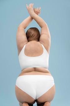 Femme surdimensionnée confiante qui pose en lingerie blanche