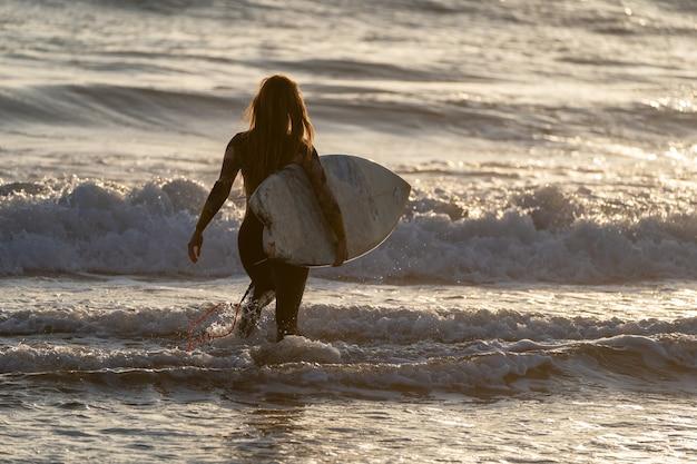 Femme surfeuse marchant dans l'océan pour surfer sur les vagues au coucher du soleil