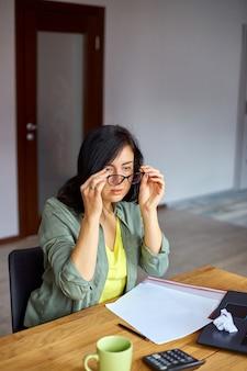 Une femme surmenée ressent une fatigue oculaire après avoir utilisé un ordinateur à la maison
