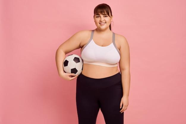 Femme en surpoids avec ballon de football, mur rose, corps positif