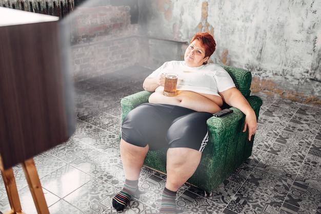 Femme en surpoids boit de la bière, boulimique, obésité