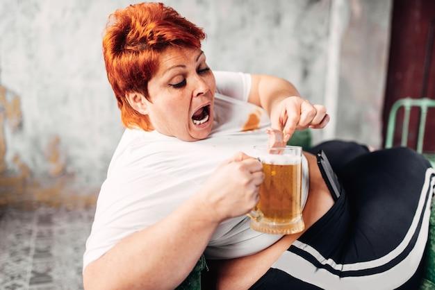 Femme en surpoids boit de la bière, obésité