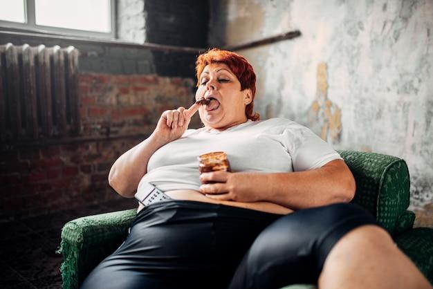 Femme en surpoids est assise sur une chaise et mange des bonbons