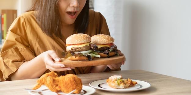 Femme en surpoids faim tenant un hamburger sur une plaque en bois, poulet frit et pizza sur table