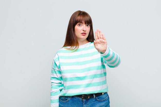 Femme en surpoids à la grave, sévère, mécontente et en colère montrant la paume ouverte faisant le geste d'arrêt