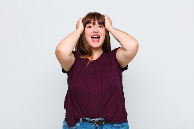 Femme en surpoids levant les mains à la tête, bouche ouverte, se sentant extrêmement chanceux, surpris, excité et heureux