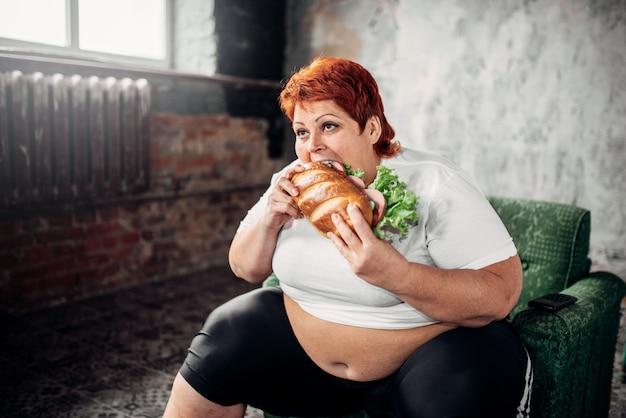 Femme en surpoids mange un sandwich, boulimique