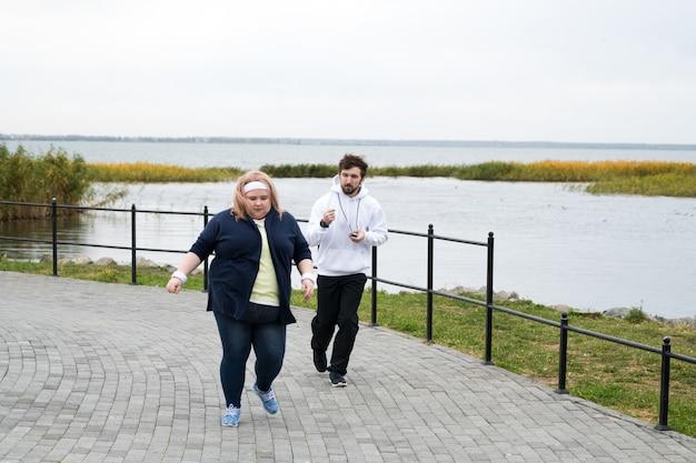 Femme en surpoids qui court dans le parc