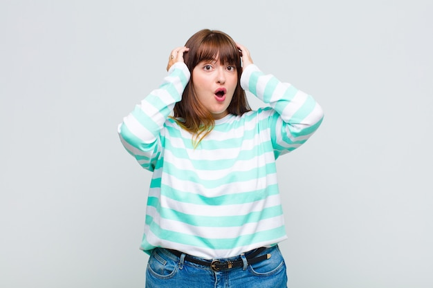 Femme en surpoids à la recherche excitée et surprise, bouche bée avec les deux mains sur la tête, se sentant comme un heureux gagnant
