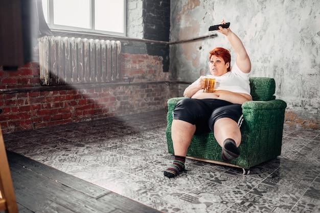 Femme en surpoids regarde la télévision, boulimique, gras