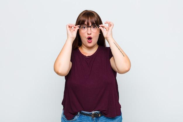 Femme en surpoids se sentant choquée, étonnée et surprise, tenant des lunettes avec un regard étonné et incrédule