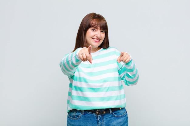 Femme en surpoids se sentant heureuse et confiante, pointant vers la caméra avec les deux mains et en riant, en vous choisissant