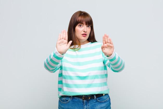 Femme en surpoids à la sérieuse, malheureuse, en colère et mécontente d'interdire l'entrée ou de dire arrêter avec les deux paumes ouvertes