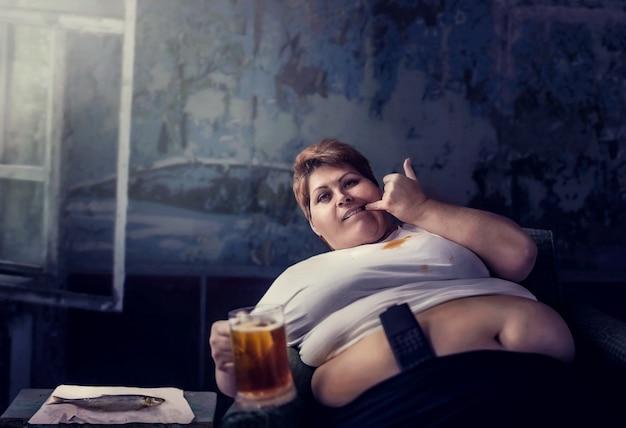 Femme en surpoids avec verre de bière, obésité