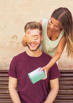 Femme surprenant son petit ami avec cadeau