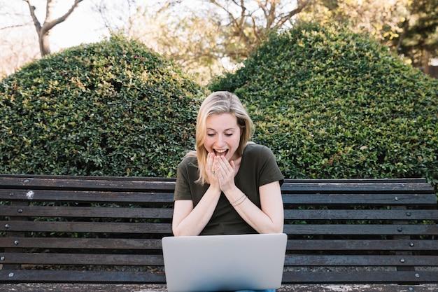 Femme surprise à l'aide d'ordinateur portable sur le banc