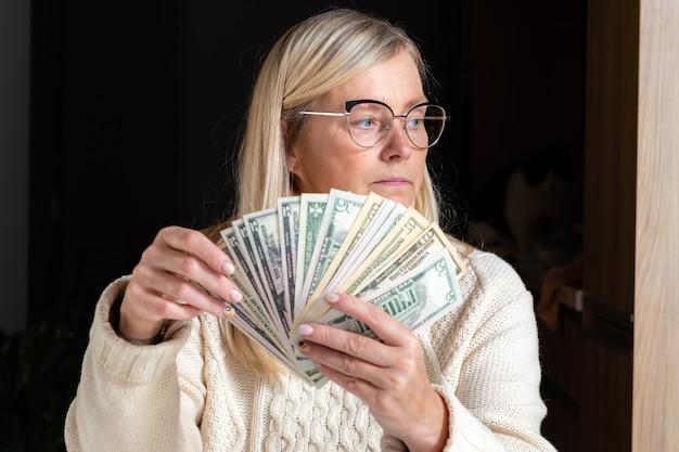 Femme surprise assise à une table et regardant les billets d'un dollar et profitant de l'argent gagné, concept de bien-être financier