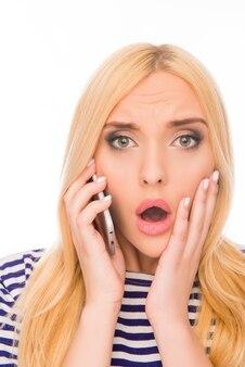 Femme surprise avec la bouche ouverte, parler au téléphone et toucher le visage
