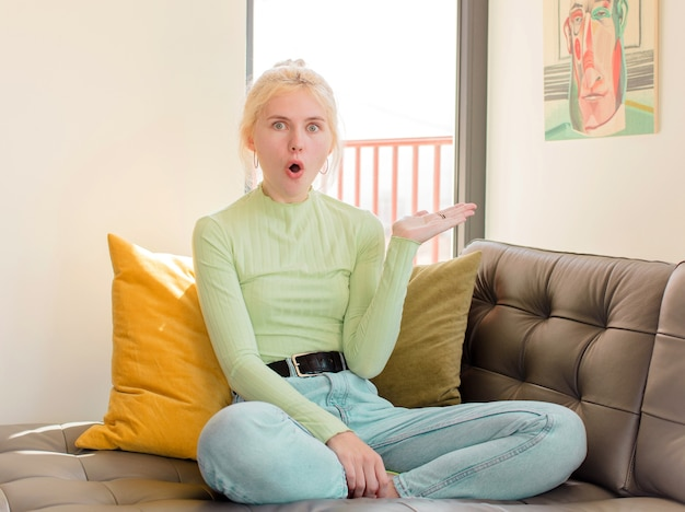 Femme à la surprise et choquée, avec la mâchoire tombée tenant un objet avec une main ouverte sur le côté