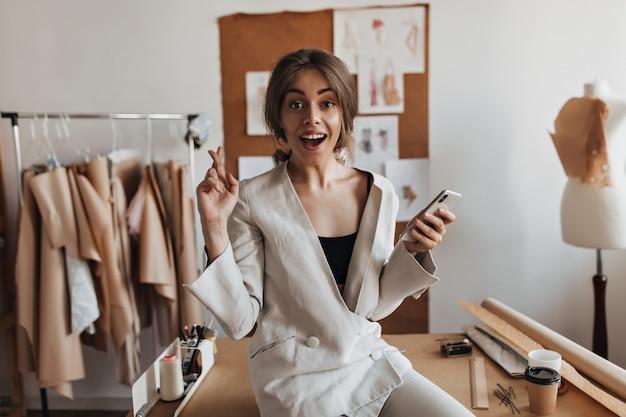 Femme surprise en costume blanc croise les doigts et tenant le téléphone
