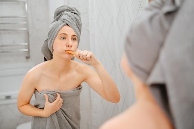 Une femme surprise dans la salle de bain se brosse les dents après une douche dans une serviette grise. concept de soins et de santé.