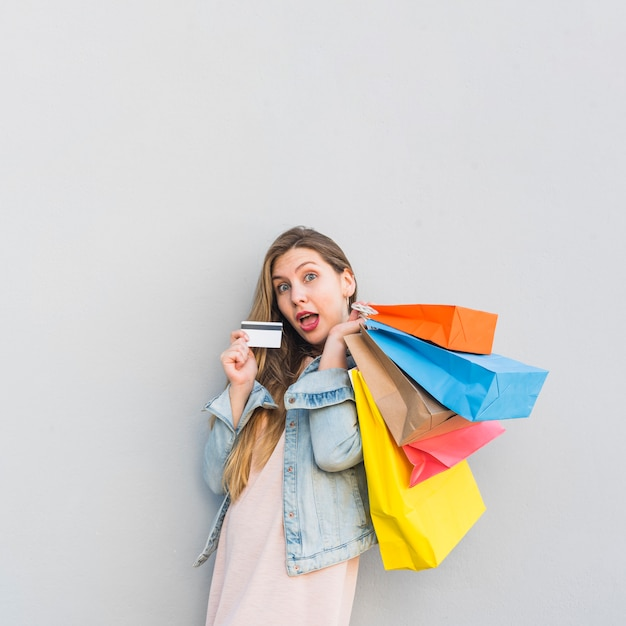 Femme surprise debout avec des sacs à provisions et une carte de crédit au mur
