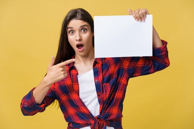 Femme surprise ou étonnée avec un panneau blanc vierge