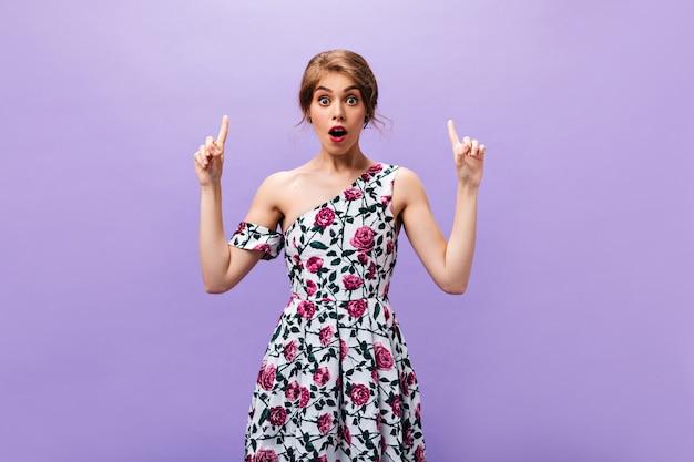 La femme surprise a une excellente idée. jolie jolie fille avec des lèvres roses dans des vêtements imprimés floraux posant sur fond isolé.