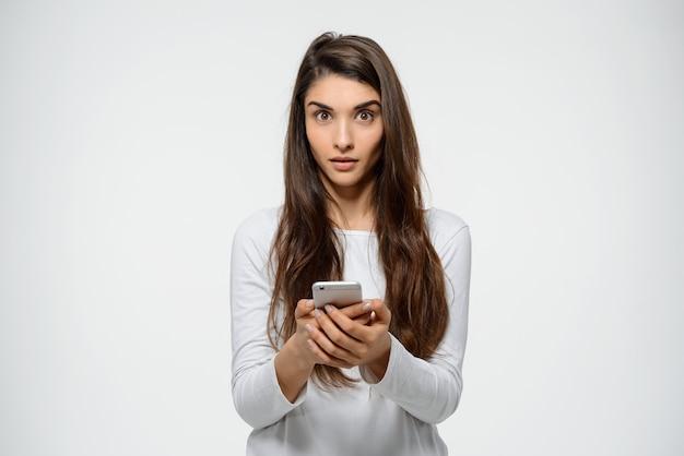 Femme surprise lire un message étrange sur le téléphone