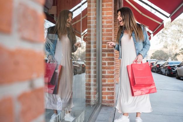 Femme surprise avec des paquets de shopping en regardant les vitrines