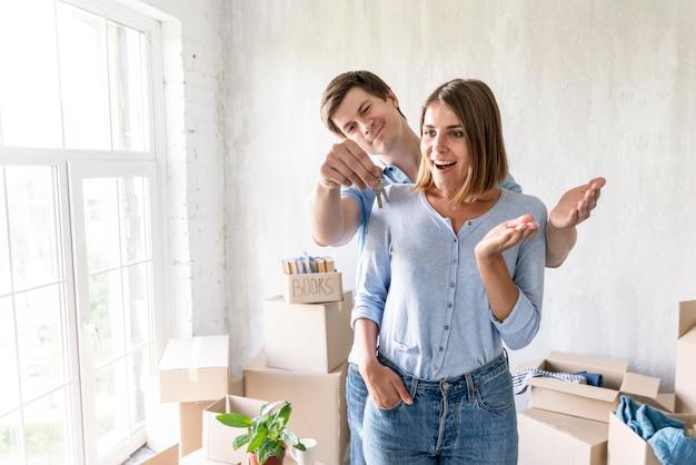 Femme surprise par partenaire avec les clés de leur nouvelle maison