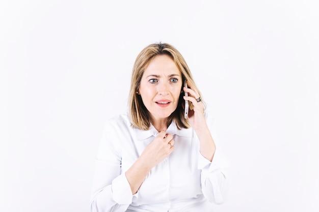Femme surprise parlant au téléphone