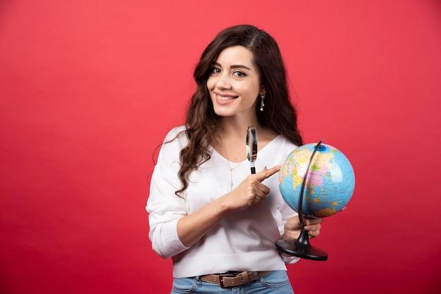 Femme surprise posant avec globe et loupe. photo de haute qualité