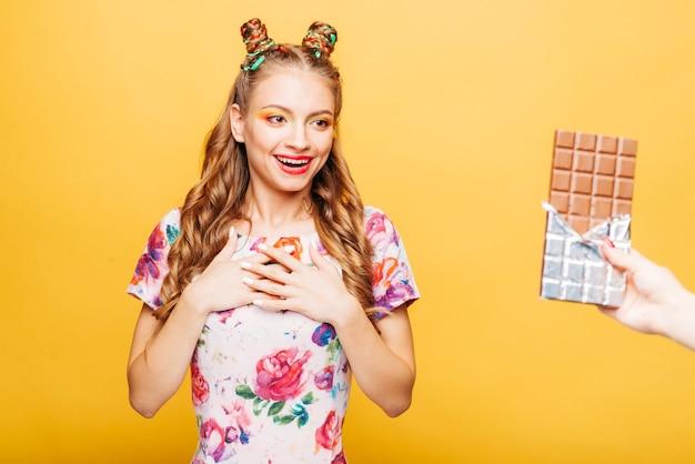 Femme surprise que quelqu'un lui donne du gros chocolat