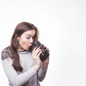 Femme surprise à la recherche dans l'appareil photo vintage sur fond blanc