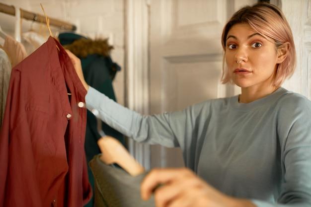 Une femme surprise reçoit des vêtements du centre de la machine à laver.