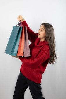 Une femme surprise en regardant ses sacs à provisions.