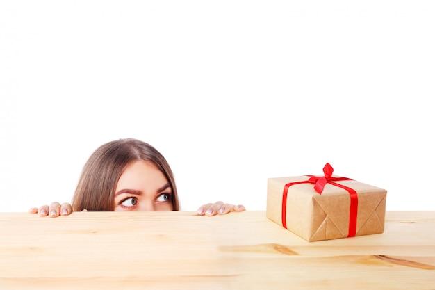 Femme surprise regarde une boîte-cadeau. noël, hiver, hiver, concept de bonheur.