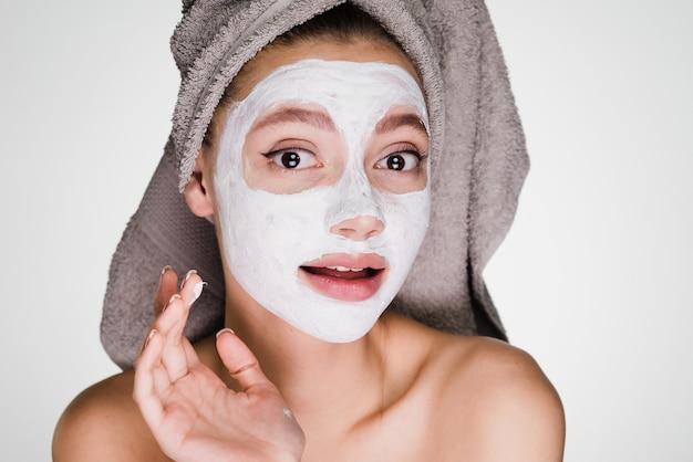 Une femme surprise avec une serviette sur la tête a appliqué un masque sur son visage