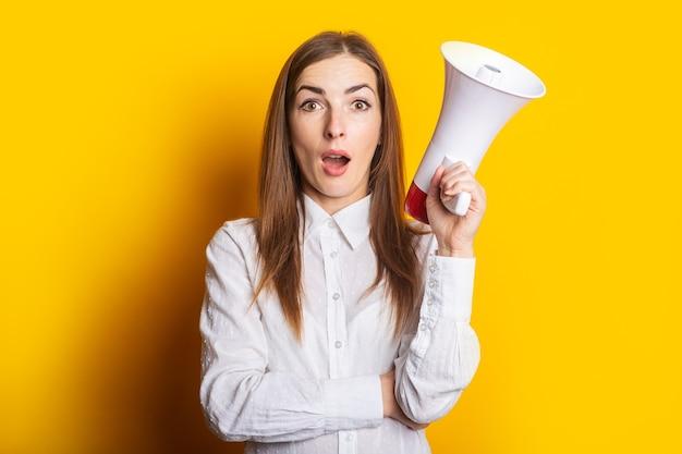 Femme surprise tenant un mégaphone dans ses mains sur fond jaune. concept d'embauche, aide recherchée. bannière.