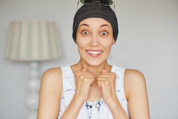Femme surprise tenant les poings fermés étonnée ou choquée par des nouvelles inattendues