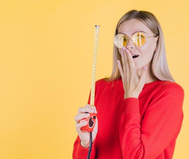 Femme surprise tenant un ruban à mesurer
