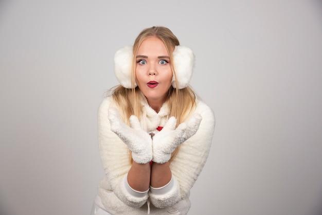 Femme surprise en tenue blanche se présentant à la caméra.