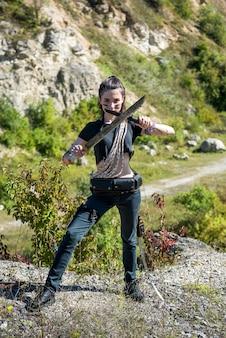 Femme survivante avec machette en tissu d'été court dans la nature, mode de vie