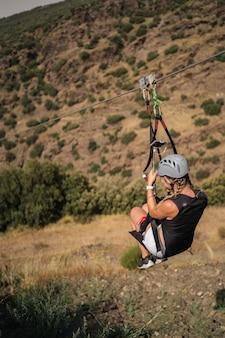 Femme suspendue à une corde. la tyrolienne est une activité d'aventure passionnante