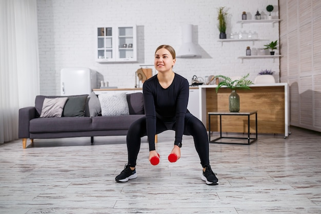 Une femme svelte fait du sport à la maison en haut et leggings. fitness à la maison pour un beau corps. exercices avec haltères pour le corps féminin. squats avec haltères pour des fesses fermes
